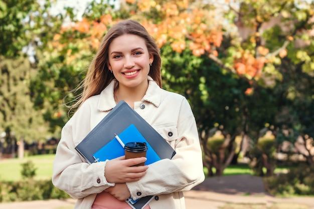 La studentessa bionda cammina nel parco con i taccuini delle cartelle e una tazza di caffè