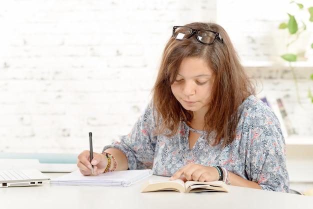 La studentessa, con gli occhiali, fa i compiti