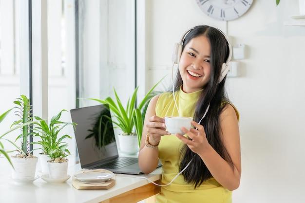 La studentessa sorridente asiatica indossa lo studio senza fili della cuffia online con l'insegnante di skype in una caffetteria,