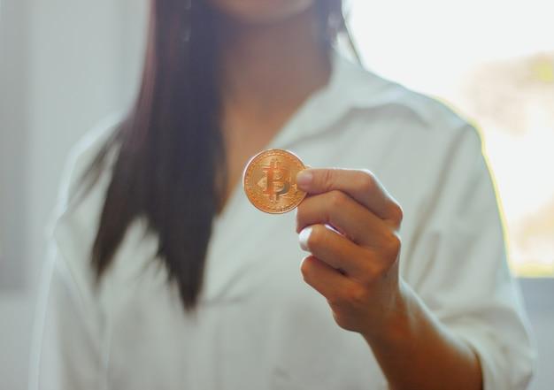 La sua mano tiene i soldi futuri di bitcoin in mano della donna. per l'era del futuro e della nuova moneta.
