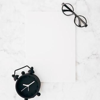 La sveglia e gli occhiali neri su carta in bianco bianca contro marmo hanno strutturato il fondo