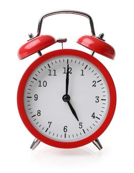 La sveglia rossa ha impostato a cinque isolato sopra priorità bassa bianca