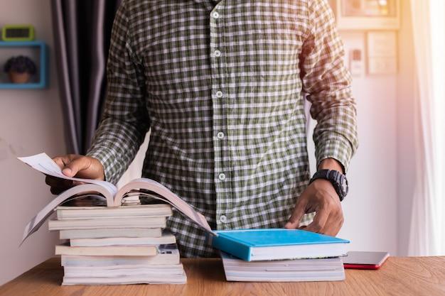 La tabella dell'ufficio con l'uomo d'affari apre un libro, leggente un libro.