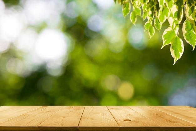 La tavola di legno con foglie sullo sfondo della natura e lo spazio della copia per inserire il testo.