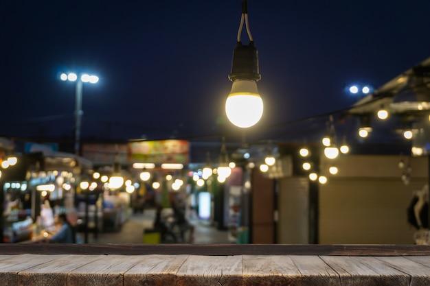 La tavola di legno davanti alle luci decorative all'aperto della corda che appendono sull'elettricità postano con la gente della sfuocatura.
