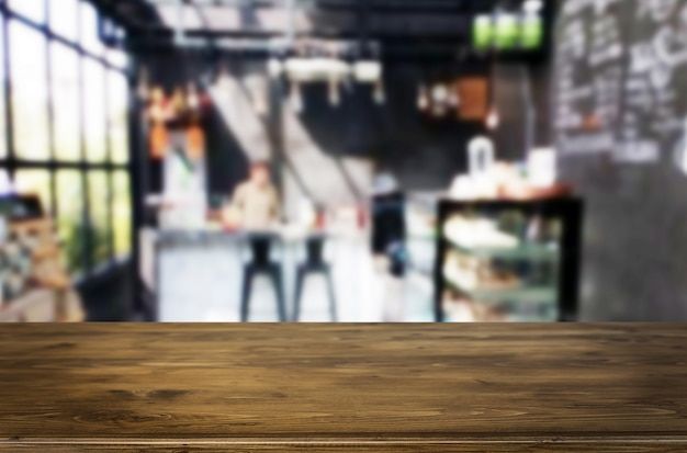 La tavola di legno marrone vuota del fuoco selezionato e la caffetteria o il ristorante sfuocano il fondo