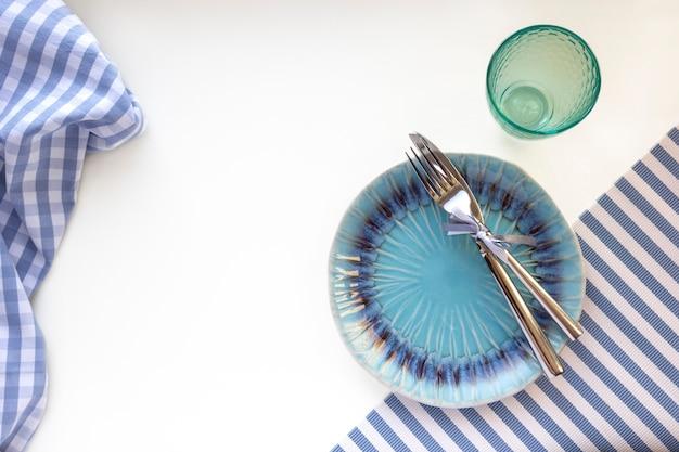 La tavola ha messo nello stile marino - piatti, vetro, forchetta e coltello vuoti sui tovaglioli a strisce, vista superiore, spazio della copia
