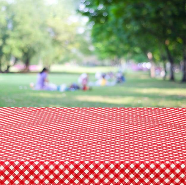 La tavola vuota e la tovaglia rossa sopra sfuocatura parcheggiano con il fondo della gente