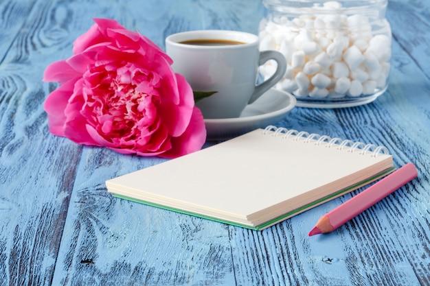 La tazza da caffè di mattina, il taccuino vuoto, la matita e la peonia bianca fiorisce sulla tavola di legno blu