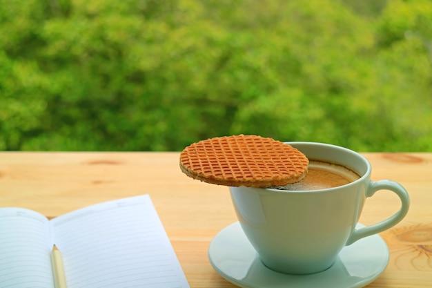 La tazza di caffè caldo con uno stroopwafel posto sulla sua cima è servita sul tavolino della finestra contro il fogliame verde sfocato