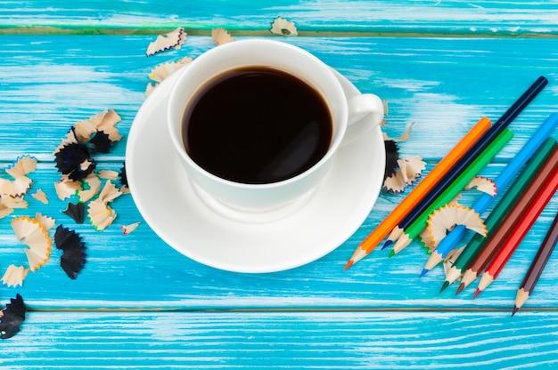 La tazza di caffè con le matite e la matita taglia su fondo di legno