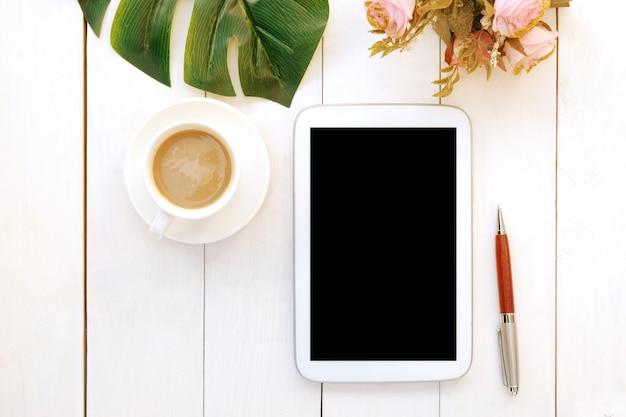 La tazza di caffè con le rose fiorisce, congedo verde e penna su fondo di legno.