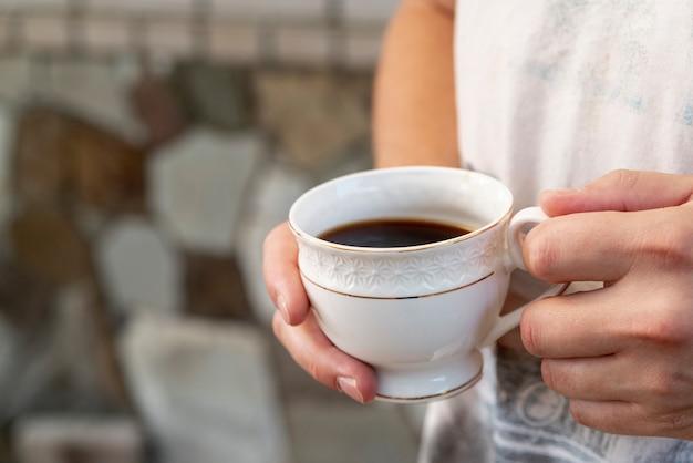 La tazza di caffè del primo piano ha tenuto dalla persona