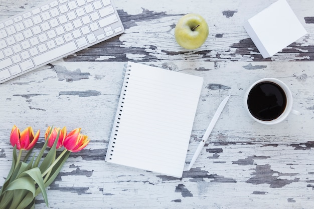 La tazza di caffè e del taccuino vicino alla tastiera ed il tulipano fioriscono sullo scrittorio grungy