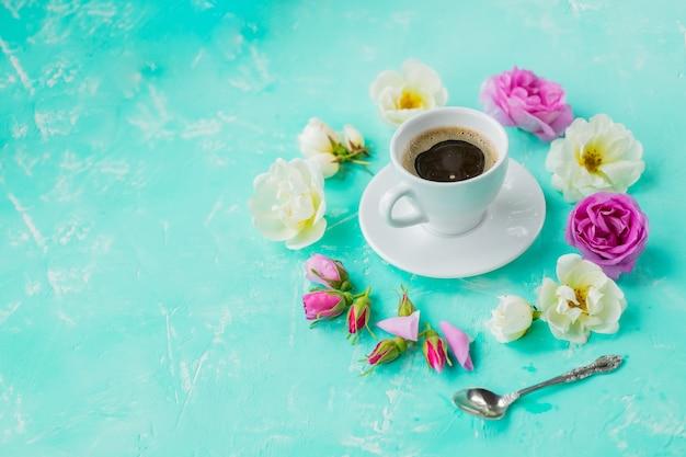 La tazza di caffè e il mazzo delle rose fiorisce su fondo pastello. vista dall'alto, surriscaldamento. composizione in stile piatto laico, layout creativo. concetto di amore, tenerezza, colazione mattutina, appuntamenti, freschezza.
