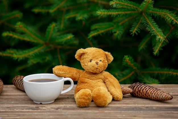 La tazza di caffè e l'orsacchiotto riguardano la tavola di legno con i rami attillati su fondo
