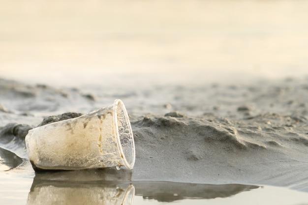 La tazza di plastica della spazzatura lasciata sulla spiaggia fa inquinamento