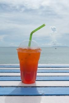 La tazza di tè del ghiaccio sulla tavola bianca ha messo sulla tavola di legno nella spiaggia