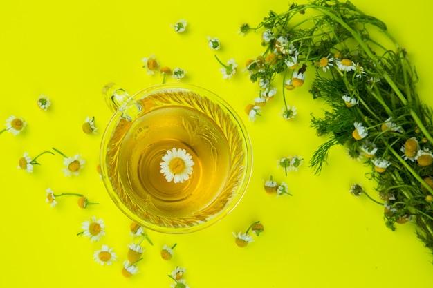 La tazza di tè di camomilla con la camomilla fiorisce nel fondo giallo