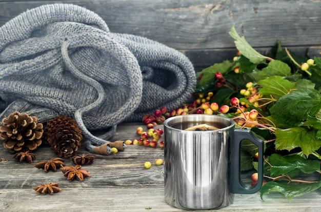 La tazza di tè su un bellissimo tavolo di legno con maglione invernale, bacche, autunno
