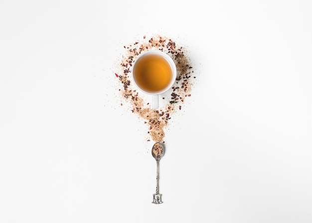 La tazza di tisana circondata con le erbe e il cucchiaio di tè secchi su fondo bianco