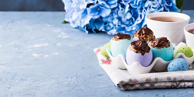 La tazza dolce di pasqua agglutina i triotti nei gusci d'uovo variopinti sul blu
