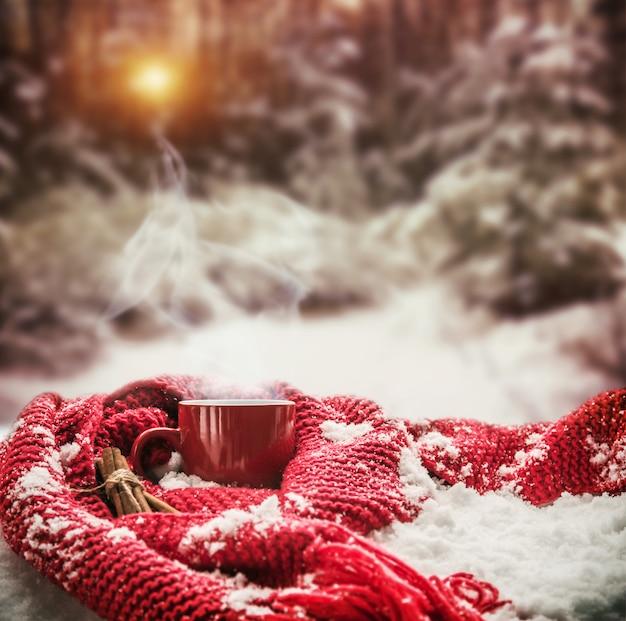 La tazza rossa con la bevanda calda sta avvolta con la sciarpa calda su neve