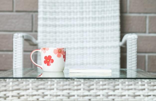 La tazza sveglia del primo piano sulla tavola di legno vaga del tessuto e la sedia hanno strutturato il fondo
