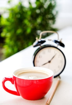 La tazzina da caffè rossa è abbinata a un orologio nero, con libri e