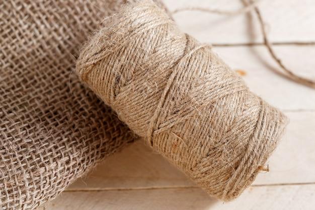 La tela e il groviglio di filo su un pavimento di legno