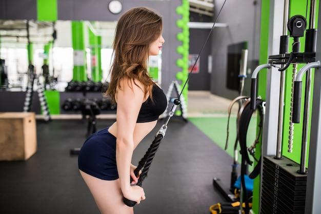 La tenera signora con un corpo in forma forte fa esercizi in palestra con simulatore di sport