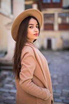 La tenera signora sorridente sta camminando per la strada e in posa in cappotti e cappello moderni e casual