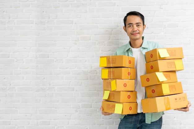 La tenuta asiatica dell'uomo porta il pacchetto o le scatole di cartone marroni sul muro di mattoni
