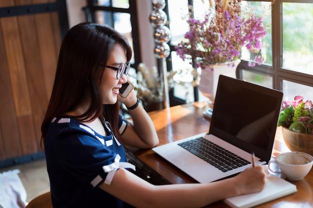 La tenuta asiatica della donna di affari prende smartphone