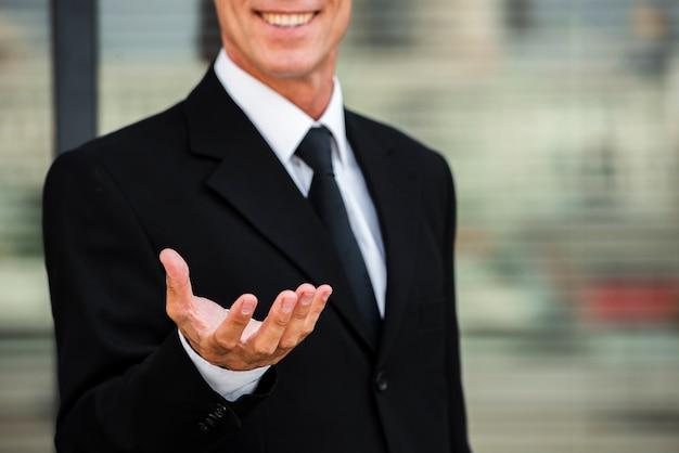 La tenuta dell'uomo d'affari distribuisce il primo piano