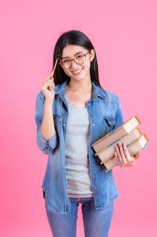 La tenuta femminile abbastanza adolescente del ritratto prenota nel suo braccio e usando la matita sul rosa, concetto di istruzione