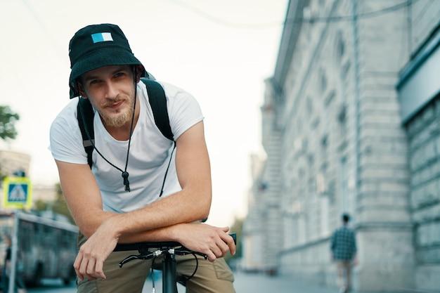 La tenuta maschio sorridente del ritratto ha attraversato le mani sul manubrio della bicicletta.
