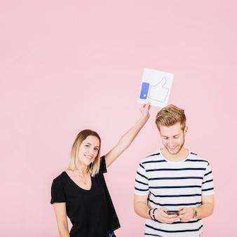 La tenuta sorridente della giovane donna sfoglia sul gesto sopra l'uomo che per mezzo dello smartphone
