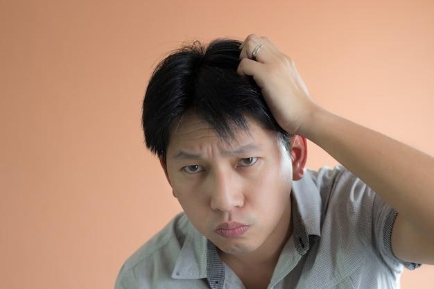 La testa di scratching dell'uomo del ritratto del primo piano assomiglia a pensare e confondere qualcosa