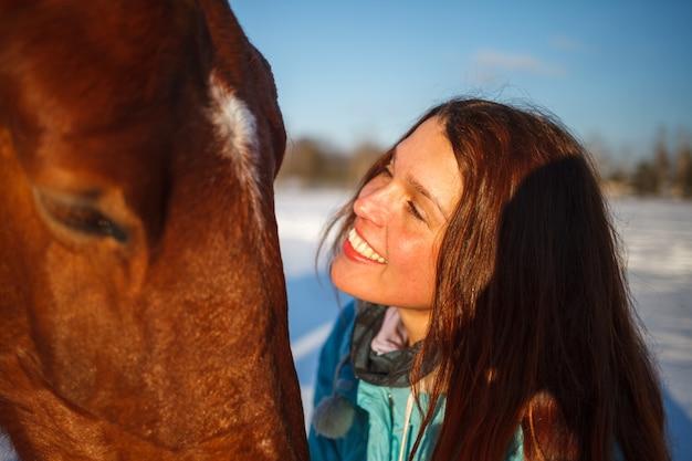 La testa di un cavallo e le mani di una ragazza si chiudono su. lei nutre il cavallo rosso