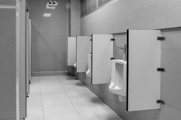 La toilette dell'uomo con la vista della toilette dagli orinatoi al vecchio tono della toilette in bianco e nero nell'ufficio.