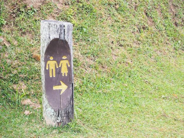 La toilette pubblica all'aperto firma su legno sopra il campo di erba nel parco nazionale.