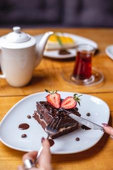 La torta al cioccolato con vista laterale con scaglie di cioccolato crema alla fragola aggiungono tè nero sul tavolo