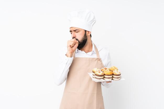 La torta del muffin della tenuta del giovane sopra la parete bianca isolata sta soffrendo di tosse e sta sentendosi male