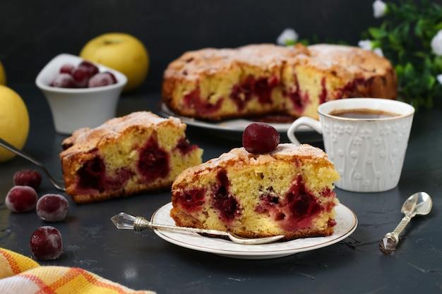 La torta di bacche con ciliegie si trova su un piatto al buio. in primo piano c'è un pezzo di torta e una tazza di caffè