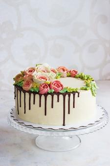 La torta di compleanno con i fiori è aumentato su superficie bianca