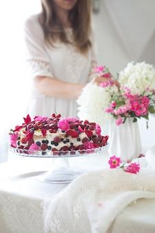 La torta di compleanno variopinta con la bacca fiorisce su un fondo bianco con lo spazio della copia