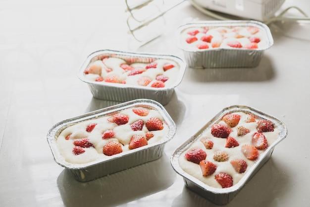 La torta di fragole nel vassoio di alluminio è pronta per la cottura.