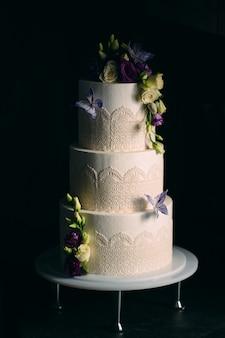 La torta è decorata con fiori sul buio