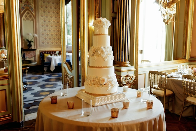 La torta nunziale bianca stanca alta sta sulla tavola rotonda